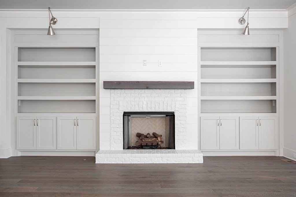 White brick fireplace, shiplap, builtin bookcases with matte finish custom wide plank hardwood flooring by Textures Nashville.