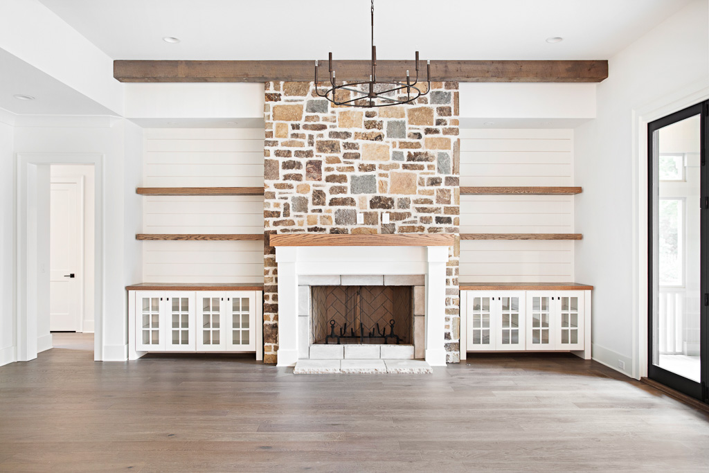 living room with stone fireplace and rustic beams featuring wide plank hardwood floors by Textures Nashville.
